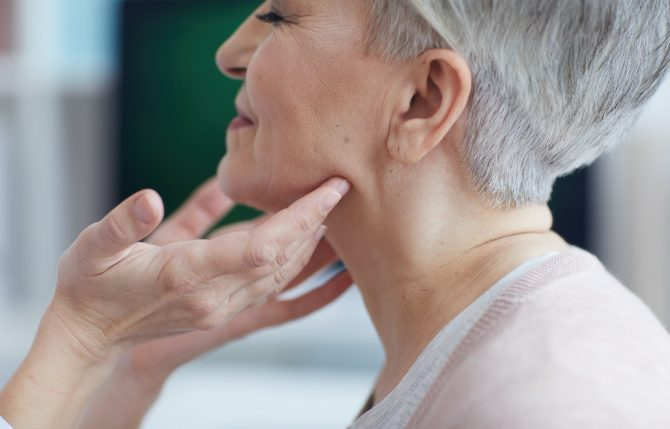 Doctor Examining Neck of Senior Woman